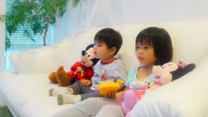 ミッキーとミニーのぬいぐるみを傍らに置きながら、食い入るようにテレビをみるふたり。真剣そのもの!